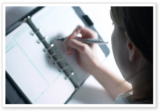 A close-up of a person writing in a planning book.